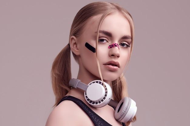 Portret pięknej blond dziewczyny z plastrami glamour na twarzy słuchania muzyki w białych słuchawkach w studio