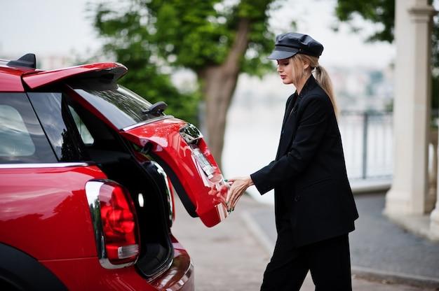 Portret pięknej blond kobieta sexy moda model w czapce iw całej czerni z jasnym makijażem w pobliżu czerwonego samochodu miejskiego umieścić jej torbę w bagażniku.