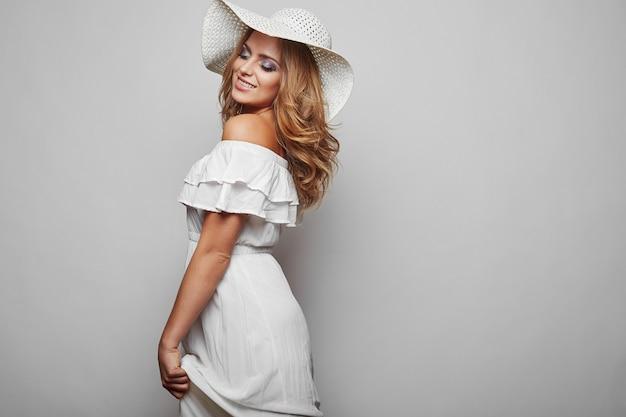 Portret pięknej blond kobieta w białej letniej sukience