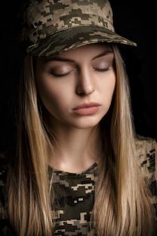 Portret pięknej blond kobiety żołnierzy w strojach wojskowych na czarnym tle