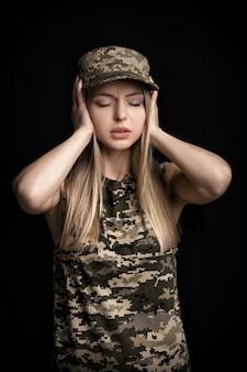 Portret pięknej blond kobiety żołnierzy w stroju wojskowym zamyka uszy rękami na czarnym tle