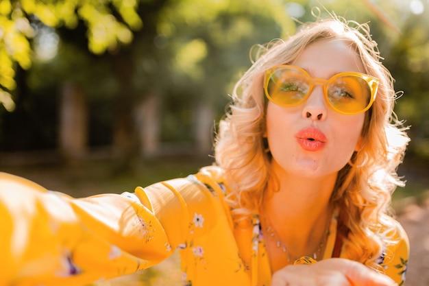 Portret pięknej blond stylowej kobiety w żółtej bluzce na sobie okulary przeciwsłoneczne przy selfie zdjęcie