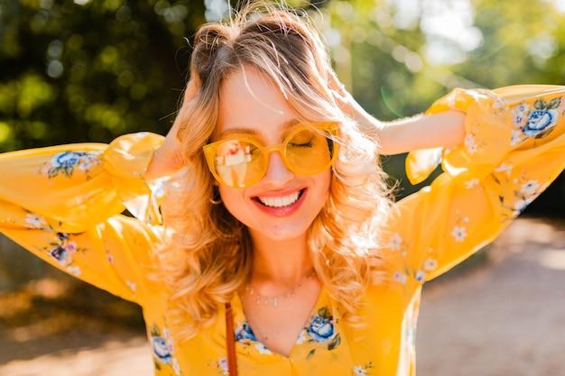 Portret pięknej blond stylowej uśmiechniętej kobiety w żółtej bluzce na sobie okulary przeciwsłoneczne