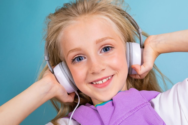 Portret pięknej blond uroczej młodej uroczej słodkiej uśmiechniętej dziecka w swobodnym wyglądzie z białymi słuchawkami, słuchając muzyki i na jasnoniebieskim tle.