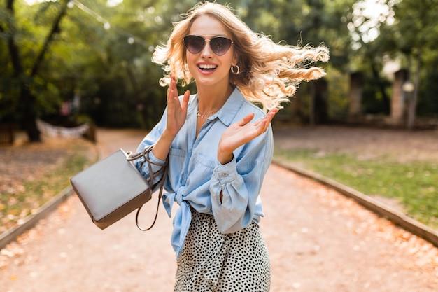 Portret pięknej blond uśmiechniętej kobiety spacerującej w parku w jasny letni dzień w stylowej niebieskiej koszuli w okularach przeciwsłonecznych i torebce, moda uliczna, śmiejąca się w radosnym nastroju