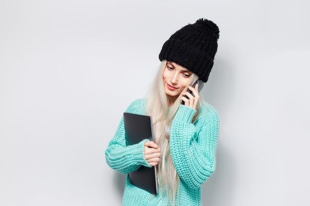 Portret pięknej blondynki dziewczyna z laptopem w rękach rozmawia na smartfonie