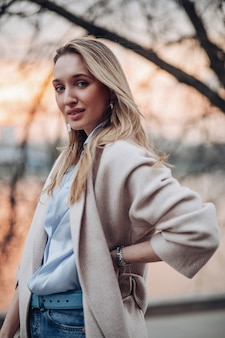 Portret pięknej blondynki kobiety pozuje do kamery jesienią