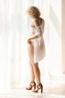 Portret pięknej blondynki kobiety stojącej w pobliżu okna i myśląc o czymś