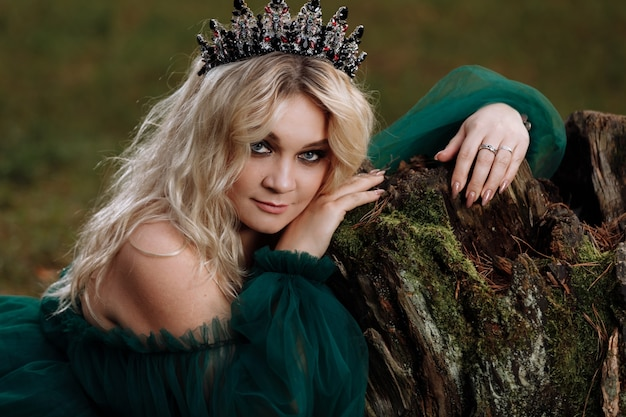 Portret pięknej blondynki młodej kobiety w zielonej sukience i diademie na głowie w lesie.