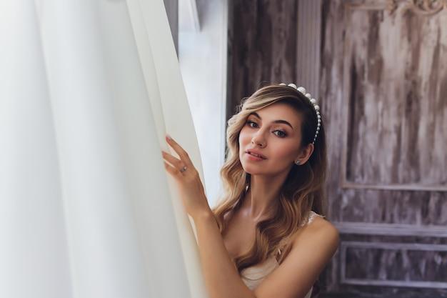 Portret pięknej blondynki panny młodej we wnętrzu. rano młoda panna młoda w szlafroku. fotografia ślubna. uśmiechnięta i śliczna dziewczyna stoi.