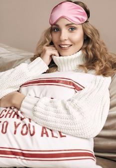 Portret pięknej blondynki w białym wełnianym swetrze i masce na oczy uśmiechnięta w jasnym, przytulnym wnętrzu