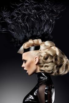 Portret pięknej blondynki z profilu, z modnie wykonanymi włosami i makijażem