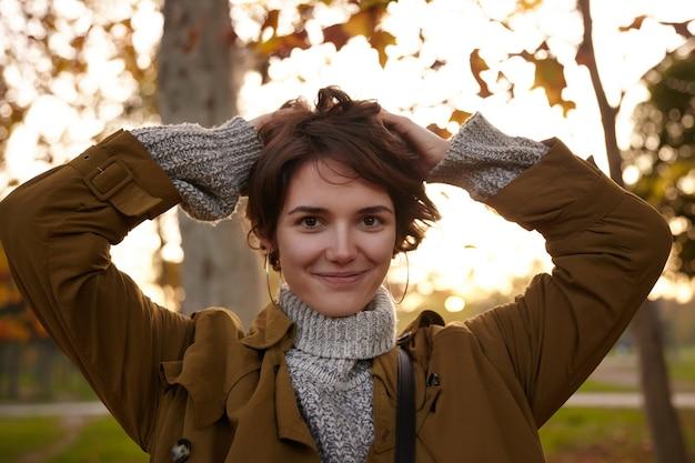 Portret pięknej brązowookiej młodej brunetki z naturalnym makijażem, trzymając podniesione ręce na głowie, patrząc pozytywnie z delikatnym uśmiechem, pozując na zewnątrz w ciepłych ubraniach cos