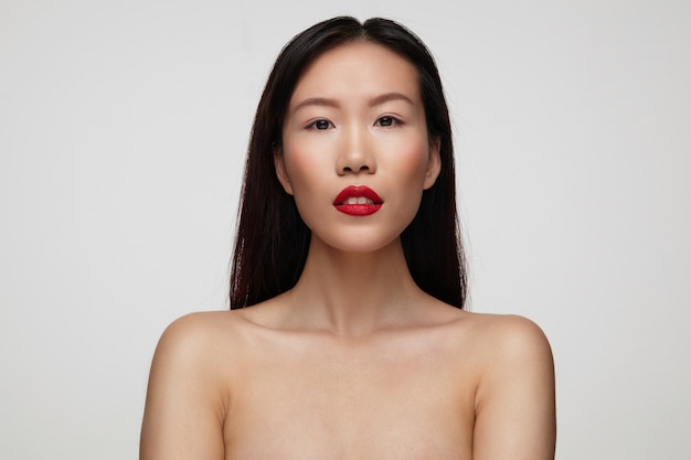 Portret pięknej brązowookiej młodej ciemnowłosej kobiety z czerwonymi ustami, patrząc spokojnie i trzymając ręce w dół, stojąc nad białą ścianą