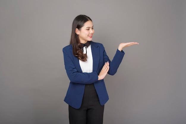 Portret pięknej brunetki biznesowa kobieta na szarym tła studiu