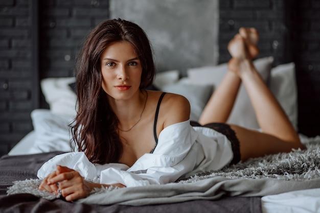 Portret pięknej brunetki dziewczyny leżącej na łóżku w bieliźnie