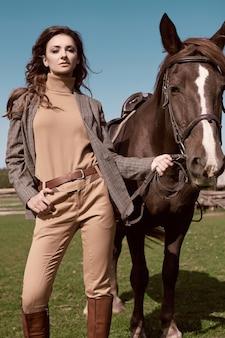Portret pięknej brunetki kobiety w eleganckiej brązowej kurtce w kratkę z koniem na wiejskim krajobrazie
