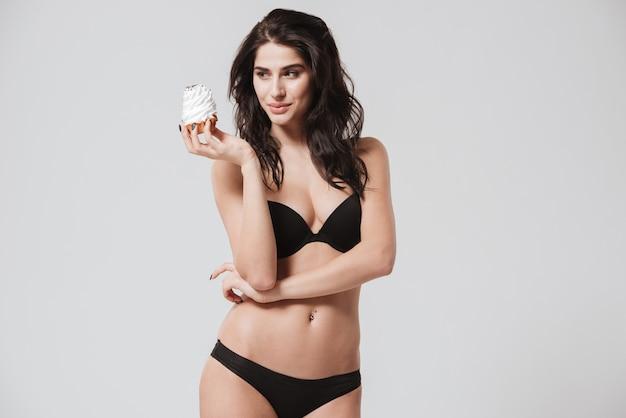 Portret pięknej brunetki kobiety w seksownej bieliźnie stojącej i patrzącej na babeczkę w ręku na białym tle