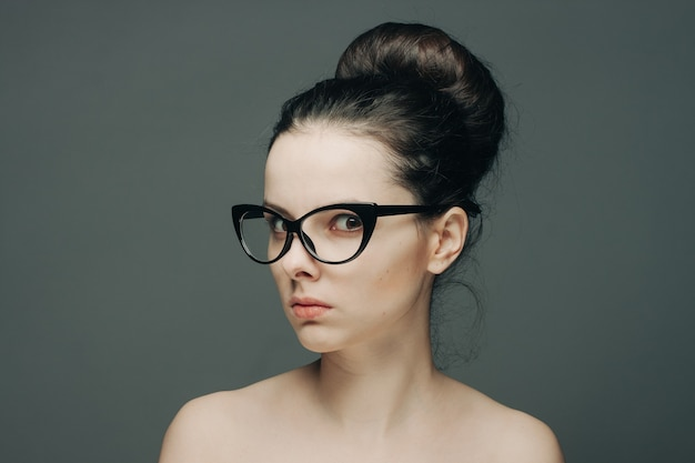 Portret pięknej brunetki kobiety z gołymi ramionami moda fryzura model przycięty widok okulary