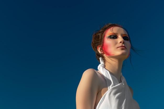 Portret pięknej, brunetki kobiety z kreatywnym makijażem