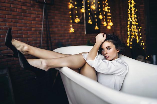 Portret pięknej brunetki leżącej w pustej łazience, trzymając nogi w górze, ubrana w białą koszulę i czarne buty