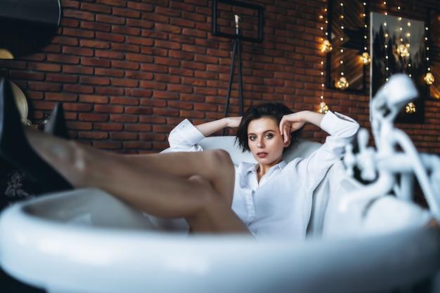 Portret pięknej brunetki leżącej w pustej łazience, trzymając nogi