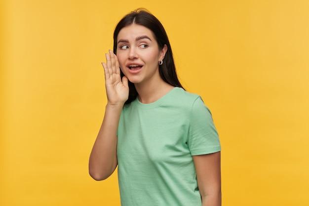 Portret pięknej brunetki młodej kobiety w miętowej koszulce trzyma ręce blisko twarzy i mówi sekret nad żółtą ścianą