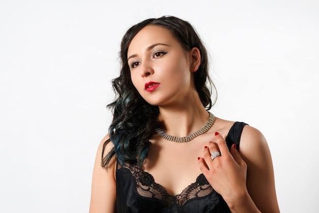 Portret pięknej brunetki młodej kobiety z lokami w naszyjniku z kryształami i dużym błyszczącym pierścionkiem na palcu. w czarnej bluzce na białym tle