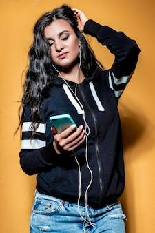 Portret pięknej brunetki, na pomarańczowym tle w rowerze i dżinsach, która słucha muzyki
