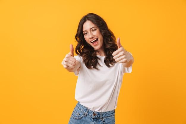 Portret pięknej brunetki ubranej w zwykłe ubrania, mrugającej i pokazującej kciuki do góry przed kamerą na białym tle nad żółtą ścianą