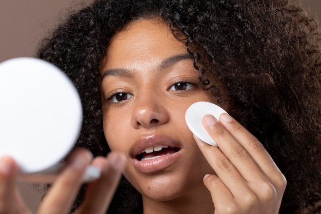 Portret pięknej czarnej kobiety wykonującej rutynową pielęgnację skóry