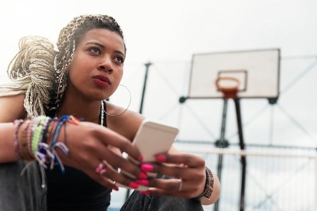 Portret pięknej czarnej kobiety za pomocą telefonu komórkowego w jej sąsiedztwie. koncepcja slumsów.