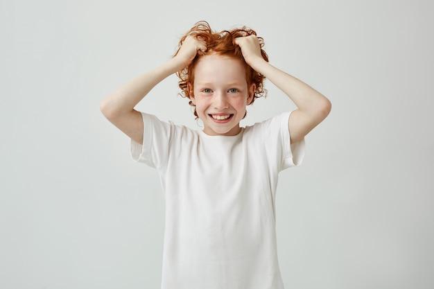 Portret pięknej czerwonej głowy dziecka z piegami, uśmiechając się jasno z zębami, trzymając włosy w ręce i patrząc