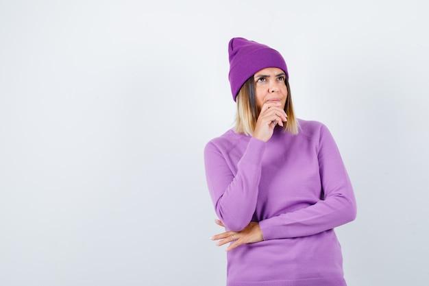 Portret pięknej damy trzymającej rękę na brodzie w swetrze, czapce i patrzącej na zamyślony widok z przodu