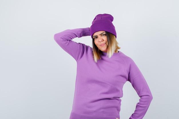 Portret pięknej damy trzymającej rękę na głowie w swetrze, czapce i wyglądającej uroczo z przodu