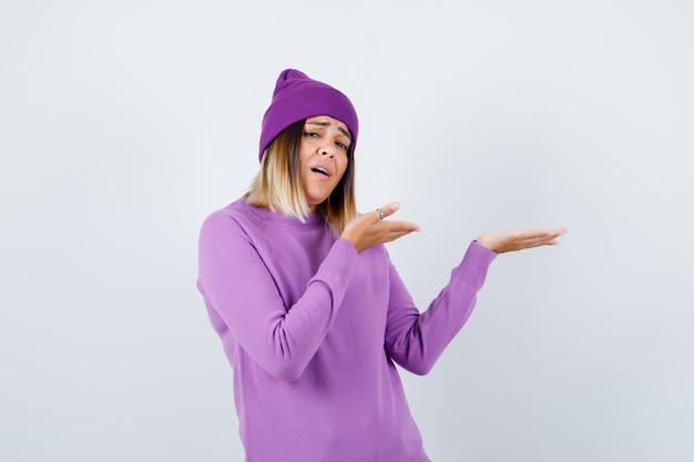 Portret pięknej damy udającej, że pokazuje coś w swetrze, czapce i wyglądającej na zakłopotany widok z przodu