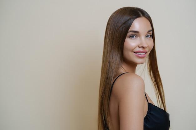 Portret pięknej delikatnej dziewczyny o zadbanych długich ciemnych włosach, ma nagie ramię, ubrany w czarną sukienkę