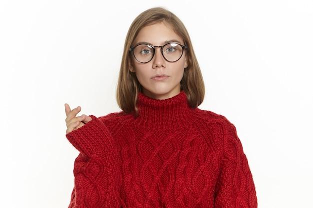 Portret pięknej długowłosej młodej kobiety w okularach i bordowym swetrze ze zdziwieniem zdezorientowanym wyrazem twarzy, wykonującym gest, myślący nad czymś, patrzący