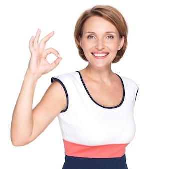 Portret pięknej dorosłej kobiety szczęśliwy z ok gestem na białej ścianie