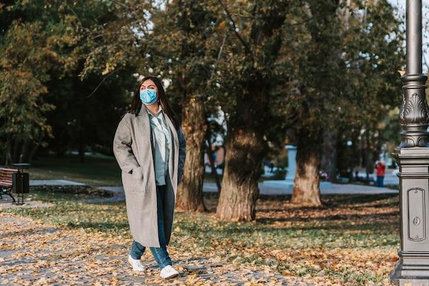 Portret pięknej, dorosłej, młodej kobiety na tle jesieni w parku w masce medycznej
