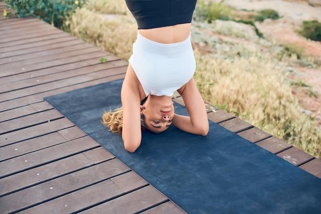 Portret pięknej dysponowanej kobiety ćwiczy joga na przebija pozycję w headstand pozie.