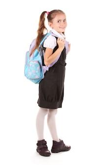 Portret pięknej dziewczynki w mundurku szkolnym z plecakiem. na białym tle
