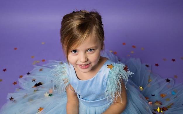 Portret pięknej dziewczynki w świątecznej niebieskiej sukience na fioletowo