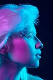 Portret pięknej dziewczyny albinos odizolowanej na ciemnym tle studyjnym w świetle neonowym