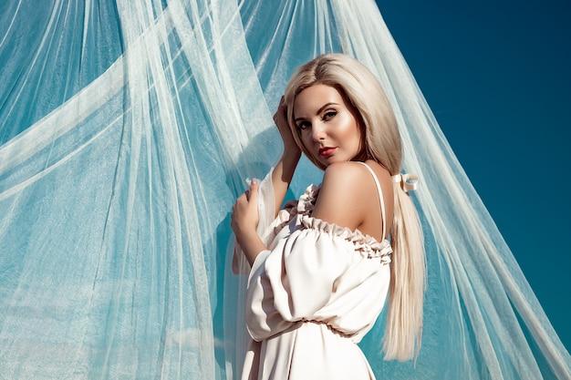 Portret pięknej dziewczyny, blondynki z długimi włosami w polu, na tle białej przezroczystej tkaniny