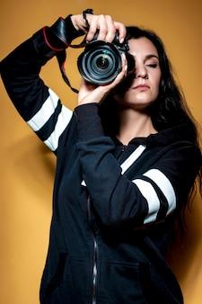 Portret pięknej dziewczyny brunetka fotograf z długimi kręconymi włosami