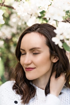 Portret pięknej dziewczyny, brunetka kobieta z zamkniętymi oczami w pobliżu kwitnącej jabłoni