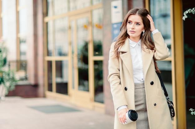 Portret pięknej dziewczyny brunetka spaceru ulicą. trzymając jednorazową zastawę stołową na wynos w jednej ręce. uśmiecha się scena miejska miasta. ciepła, słoneczna jesienna pogoda. na ulicy