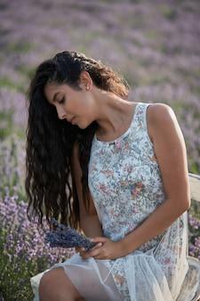 Portret pięknej dziewczyny brunetka w lawendowym polu. letni model lawendy pozuje przed kamerą.