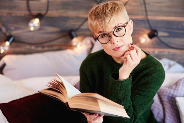 Portret pięknej dziewczyny, czytając książkę w łóżku